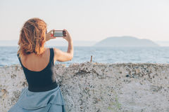 Young woman taking a photo using smartphone. By the seaside Stock Image