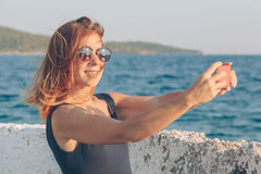 Young woman taking a photo using smartphone. By the seaside Royalty Free Stock Photography