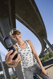 Young woman taking photograph beneath overpasses, smiling, portrait, low angle view. Young women taking photograph beneath overpasses, smiling, portrait, low Royalty Free Stock Photo