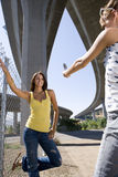 Young woman taking photograph of friend by fence beneath overpass, low angle view Royalty Free Stock Photos