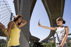 Young woman taking photograph of friend by fence beneath overpasses, low angle view. Young women taking photograph of friend by fence beneath overpasses, low Royalty Free Stock Image