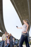 Young woman taking photograph of friends on bonnet of car beneath overpass, low angle view Royalty Free Stock Photos