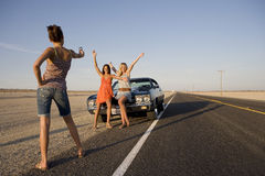 Young woman taking photograph of friends by car on open road, low angle view Royalty Free Stock Image
