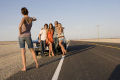 Young woman taking photograph of medium group of friends by car on open road, low angle view Royalty Free Stock Photos