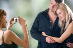 Young woman taking photograph and young embracing couple, posing. Focus on girl with photo camera Stock Photo