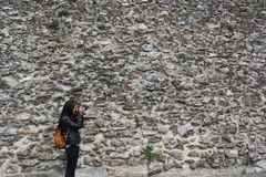 YOUNG WOMAN TAKING PHOTOGRAPHS, STONE WALL BACKGROUND stock photo