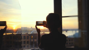 Young woman Taking Photos Of City on Mobile Smart Phone at window. Stock Photo