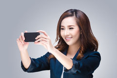 Young woman is taking photos with the mobile phone Stock Image