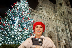 Young woman taking photos near Christmas tree in Florence, Italy. Young woman in white coat taking photos while standing in front of Christmas tree near Duomo in royalty free stock photo