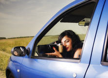 Young woman taking photos with telephoto lens. Illustrating surveillance royalty free stock image