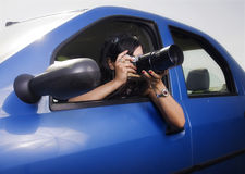 Young woman taking photos with telephoto lens. Illustrating surveillance stock images
