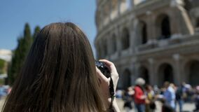 Young woman taking picture of Colosseum on camera, enjoying hobby on vacation stock video footage