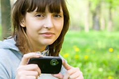 Young woman taking picture with digital camera Stock Images