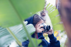 Young woman taking a picture in a forest Stock Photo