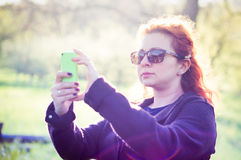 Young woman taking picture with green smartphone Royalty Free Stock Photos