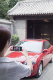 Young Woman Taking a Picture of Her Car Stock Photography
