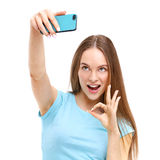 Young woman taking a picture of herself with her camera phone. Beautiful young woman taking a picture of herself with her camera phone - isolated on white Royalty Free Stock Photography