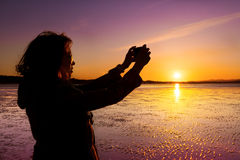 Young woman taking picture of herself, selfie, on a beach during sunset. Royalty Free Stock Photo