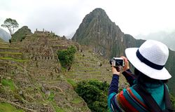Young woman taking picture of the Inca ruins in Machu Picchu, UNESCO world heritage site in Cusco region of Peru. Archaeological site royalty free stock photo