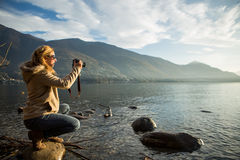 Young woman taking picture by the lake Royalty Free Stock Image