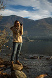 Young woman taking picture by the lake Royalty Free Stock Images