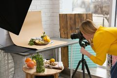 Young woman taking picture of lemons, mint. And ginger in professional studio. Food photography royalty free stock photo