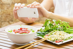 Young woman taking a picture the Pho Bo on smartphone in Vietnam Stock Photography
