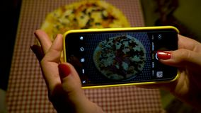 Young woman taking picture of pizza with smartphone. Woman make photo of pizza. Young woman in a restaurant make photo of food with mobile phone camera. Woman stock footage