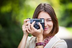 Young woman taking picture with retro camera Royalty Free Stock Photography