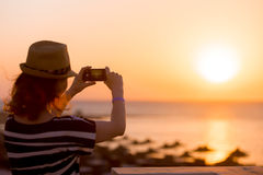 Young woman taking picture of sea sunrise Stock Photo