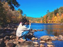 A young woman taking pictures of the autumn views. By housatonic river in New England Connecticut United States royalty free stock photography