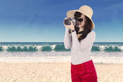 Young woman taking pictures at beach Stock Photo