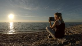 Young woman taking pictures on the beach using tablet. Young woman with tablet is sitting on the beach enjoying beautiful sunset and making pictures of the stock video