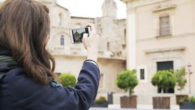 Young woman is taking pictures of a building in Valencia with her phone stock footage