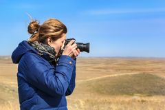 Young woman is taking pictures at the camera on a blue sky background. Background blur. place for text Royalty Free Stock Photography