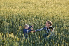 Young woman taking pictures of a child in a field Royalty Free Stock Photography