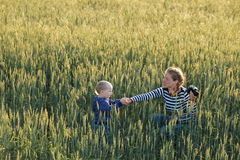 Young woman taking pictures of a child in a field Stock Photography