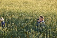 Young woman taking pictures of a child in a field Stock Image