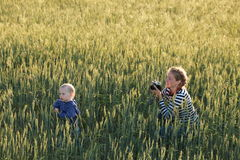 Young woman taking pictures of a child in a field Stock Photo