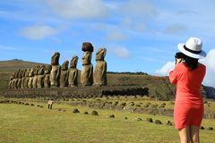 Young woman taking pictures of the famous Moai statues at Ahu Tongariki on Easter Island. Archaeological site in Chile stock images