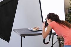 Young woman taking pictures of food in   photo studio. Young woman taking pictures of food in professional photo studio Royalty Free Stock Image