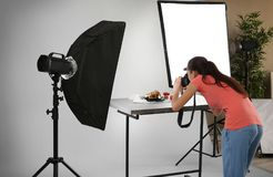 Young woman taking pictures of food in professional   studio. Young woman taking pictures of food in professional photo studio Stock Image