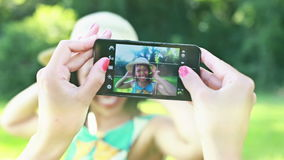 Young woman taking pictures of her friend with phone. View of woman's hand holding a mobile phone and taking pictures of her friend dancing and posing in the stock video