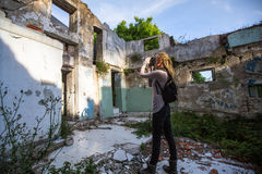 Young woman taking pictures of ruins abandoned buildings. Travel. Stock Photos