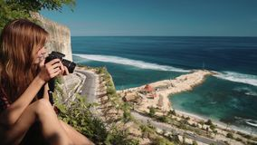 Young woman taking pictures sitting on edge of cliff overlooking road and ocean stock video footage