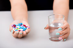 Young woman taking pill or drug with glass of water, Royalty Free Stock Photography