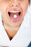 Young woman taking a pill Stock Images