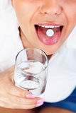 Young woman taking a pill Stock Photography