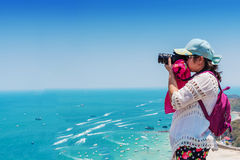 Young woman is taking a sea photo on clear sky day Royalty Free Stock Image