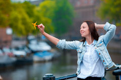 Young woman taking self portrait in european city outdoors. Young adult holding smartphone camera to take a picture of Stock Photo